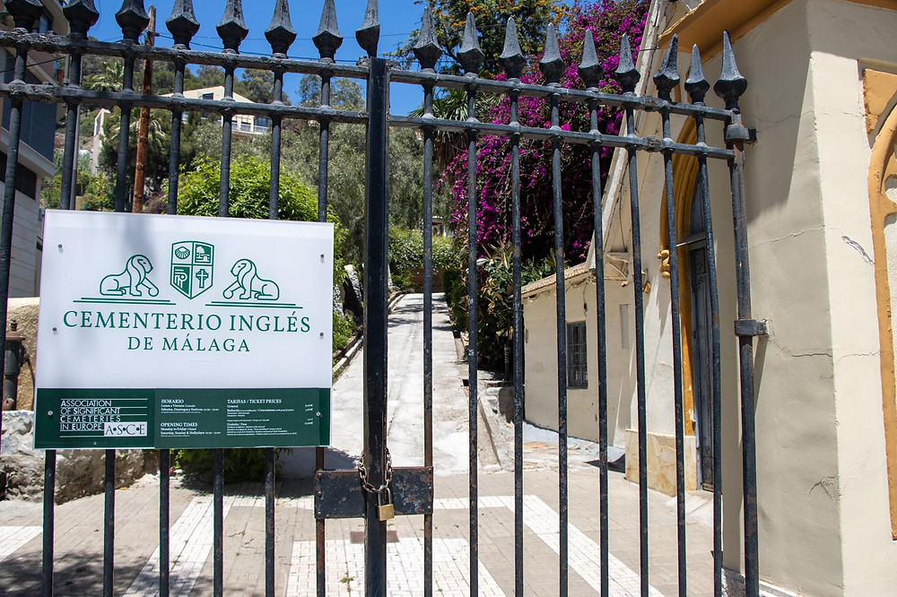 Entrance gate to an English cemetery in Spain with a sign on the gate in white and green.