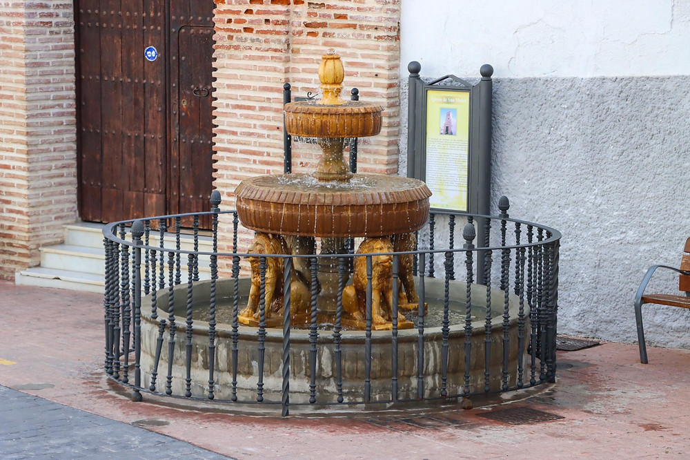 Small fountain in front of the church with golden lions across the bottom, surrounded by an iron fence.