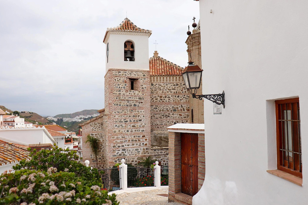 View of the town church from mid-level on a view platform. A brick and stone church with a white painted tower top.