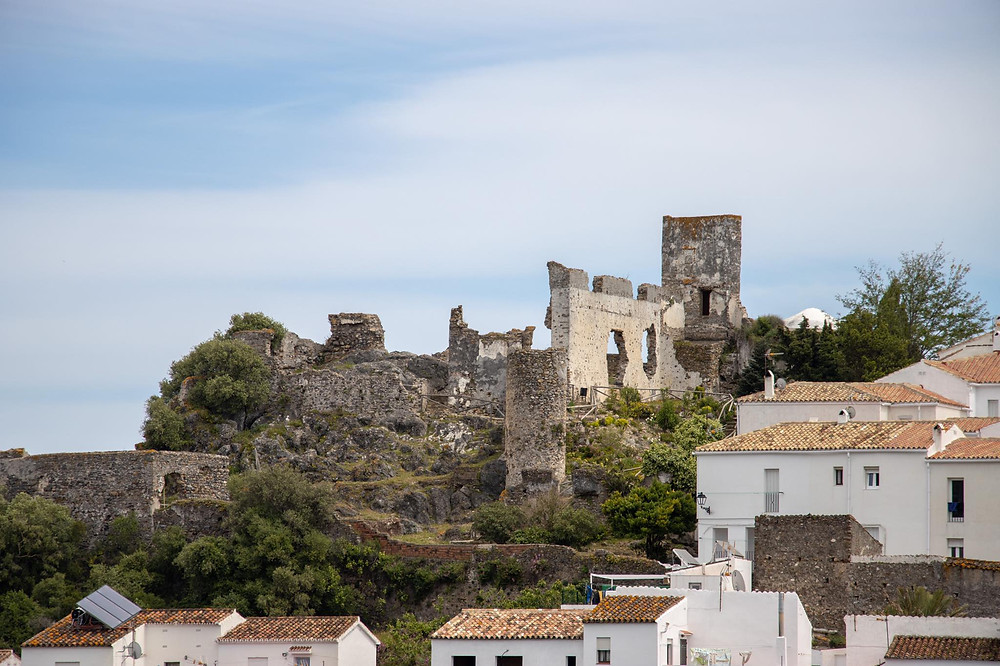Medieval ruined castle on a hill with whitewashed houses below.