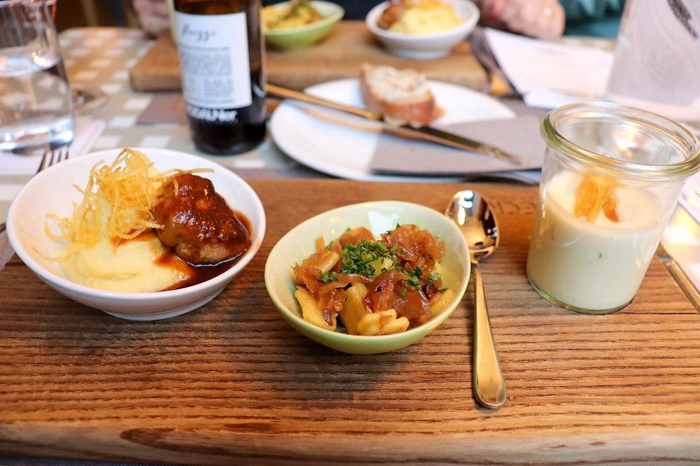 Small dishes of potatoes and meat, pork, and a soup on a wooden board.