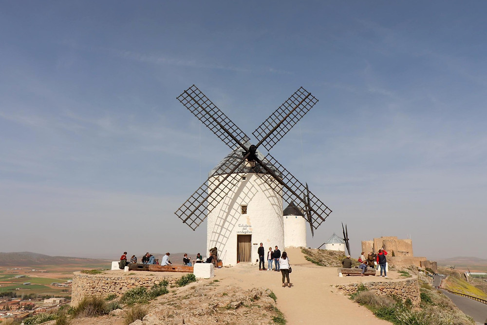 Full length view of a white stone painted windmill with people around the outside sitting down and eating.