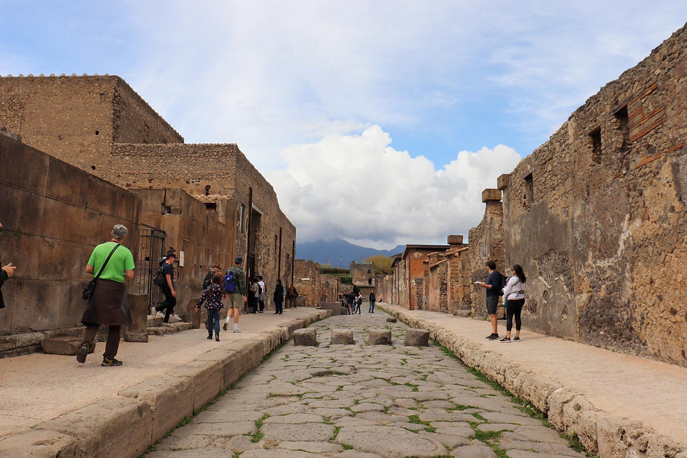 A street in Pompeii with a few tourists, lined with stone buildings and large stones on the floor to make a road.