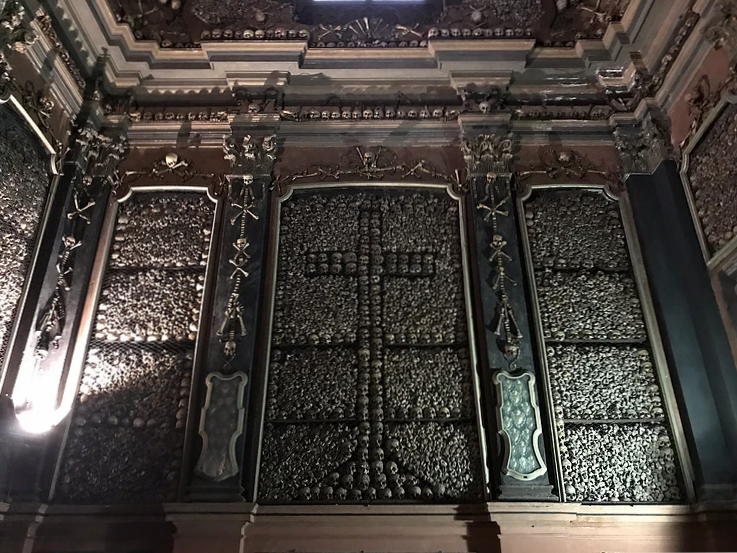 Inside the San Bernardino alle Ossa showing the room full of skulls and bones along the walls and ceiling, a free site to visit in Milan.