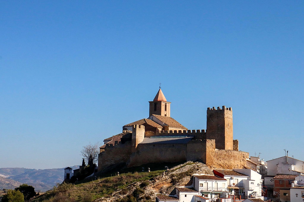 View of Castillo de Iznájar with the church in the background from a viewpoint. The castle sits high up on a hill overlooking the rest of the city.
