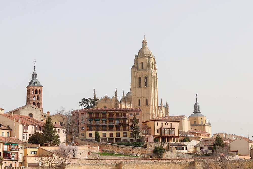 View of the city of Segovia from a viewing platform, looking back at the tower of the cathedral and other buildings.