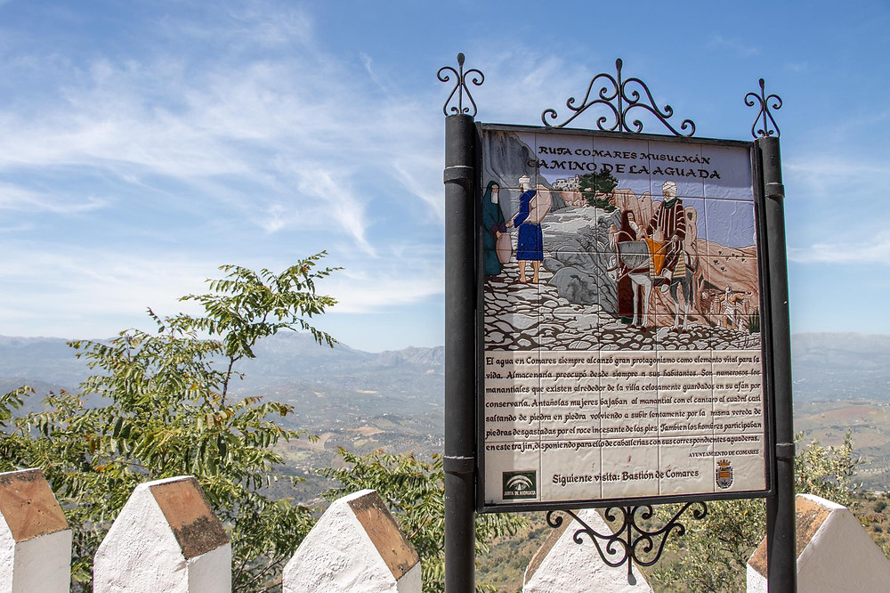 Tiled ceramic panel showing a scene from Comares' history with text under it, sitting at a viewpoint.