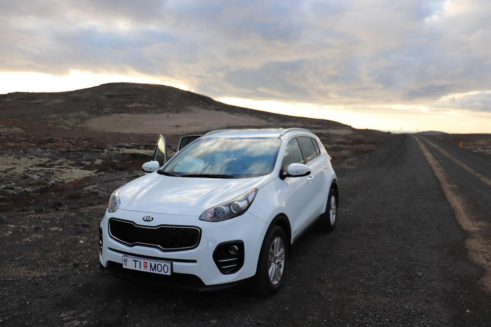 White KIA Sportage on a dirt road in Iceland at sunset