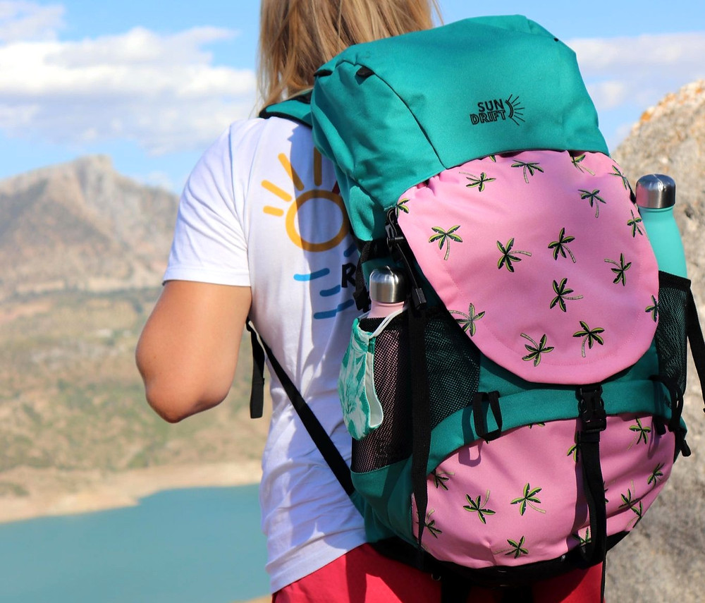 Panglao 55L Backpack in pink and teal being worn at a hiking viewpoint in Spain