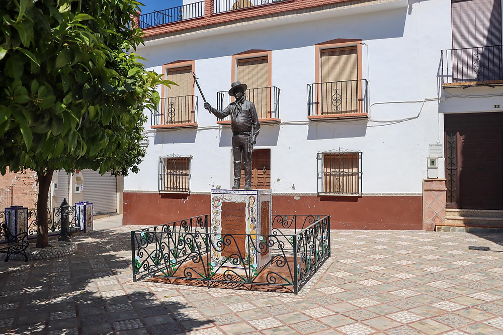 A whitewashed hermitage with a statue of a man outside of it in the small plaza.