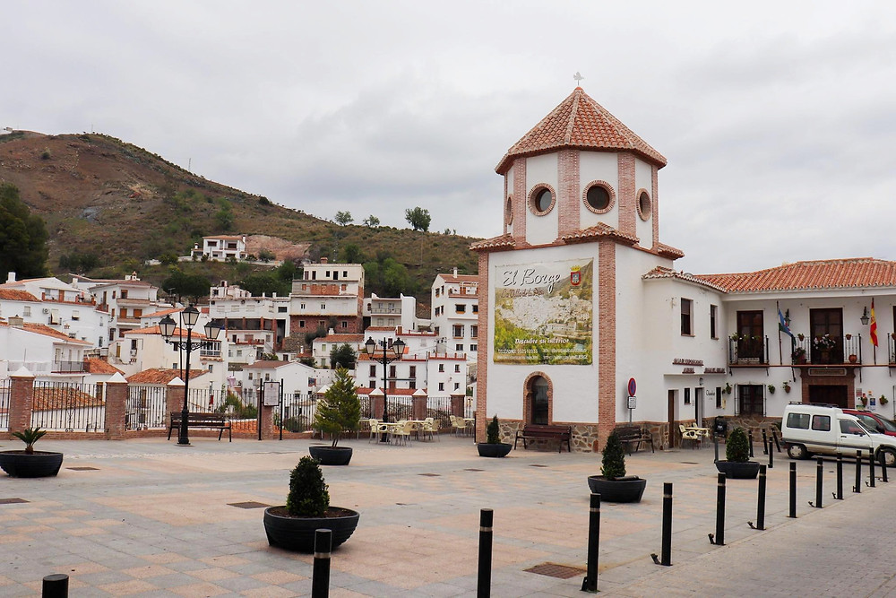Open plaza space with a white building on the right and a viewpoint of the white village buildings and the hills behind it.