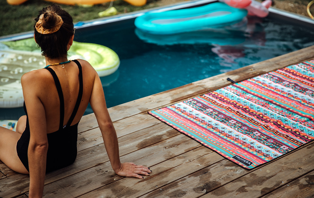 Multi-coloured quick drying towel on the ground next to the pool with a woman sitting next to it