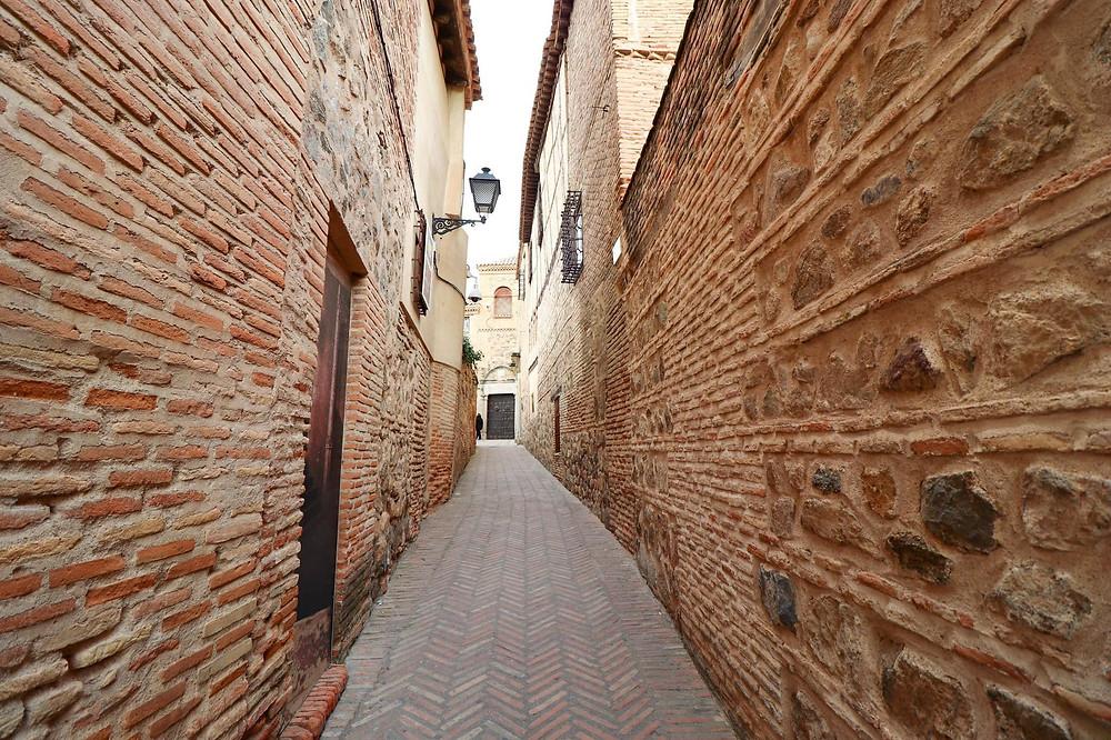 Orange bricked narrow medieval street with arrow shaped bricks on the ground.