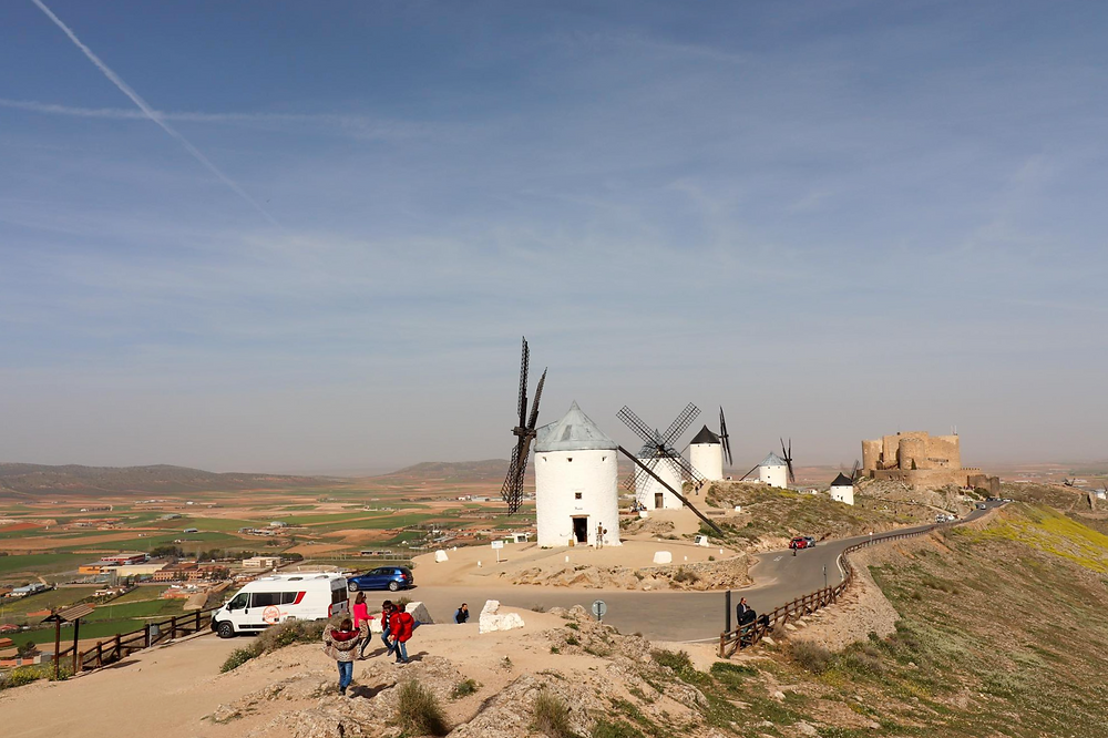 Consuegra windmills all in a line with the castle in the background and the parking lot in the forefront. The view is from above with the landscape rolling out in front.