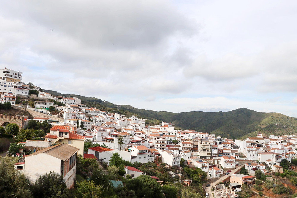 View of a white village slanting down a hill on a cloudy day.