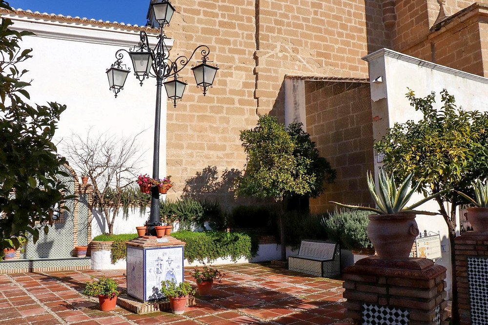 Small plaza next to the church decorated with plants and flowers, as well as white and blue tiled photos. There is a large vintage lamppost in the middle of the plaza.