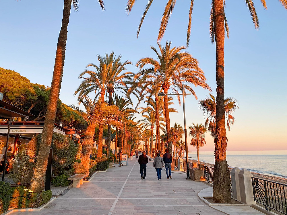 Paseo Maritimo, a long seafront promenade at sunset with an orange glow on the palm trees.