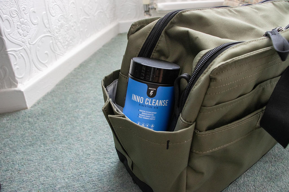 Supplment bottle in the side pouch of a green duffel bag.