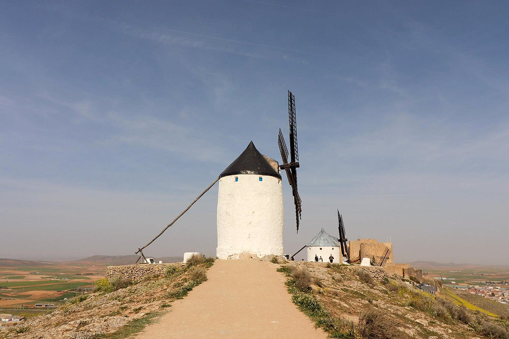 White stone painted windmill from the side with a medieval castle in the background and a hilly landscape.