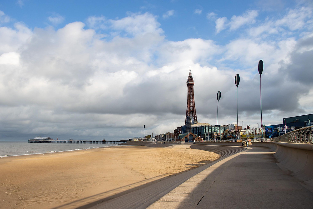 A promenade next to a beach with Blackpool Tower in the distance.