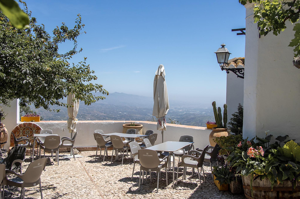 Outdoor dining area in a small courtyard within a hotel, with a view of the mountains and Málaga's landscape.