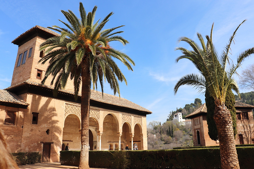 Palm trees and building inside the Nasrid Palaces in the Alhambra in Granada, Spain