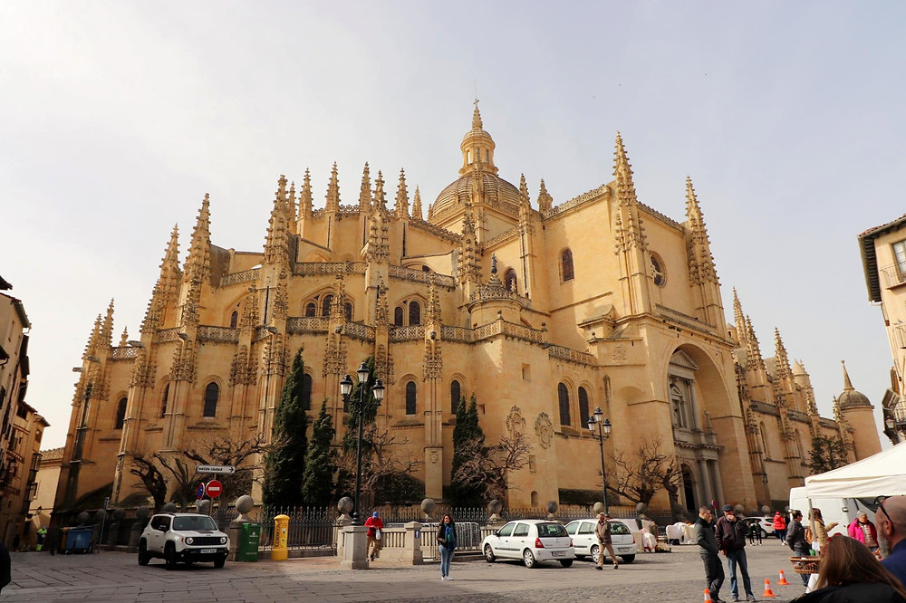 Large medieval cathedral with a series of spiked corners and a large dome in the middle, all in yellow brick.