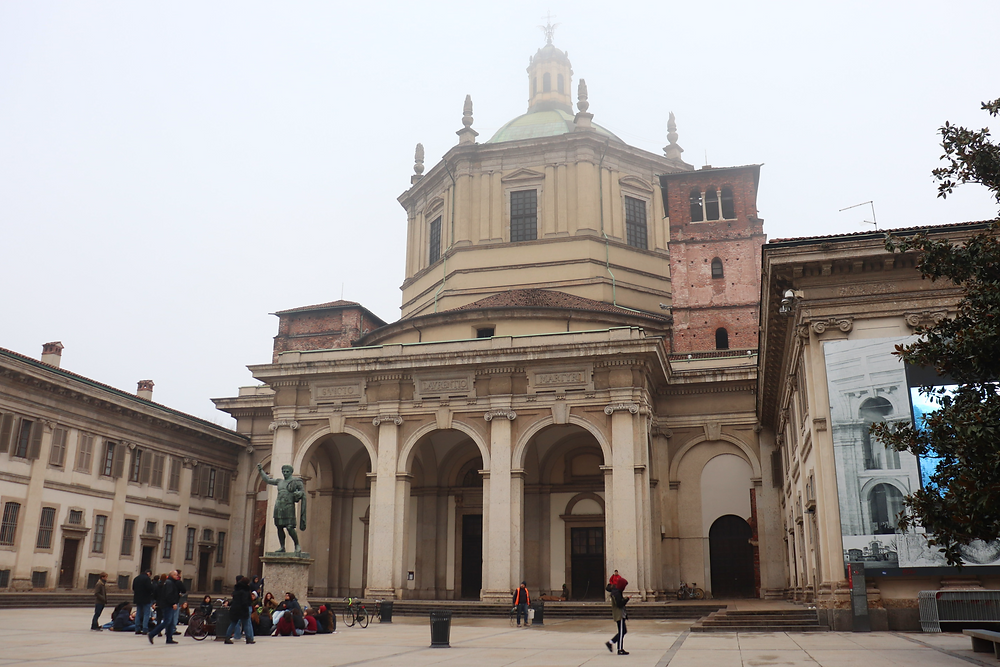 Basilica di San Lorenzo on a foggy day with a crowd of tourists in front of it, a free plaza to visit in Milan.