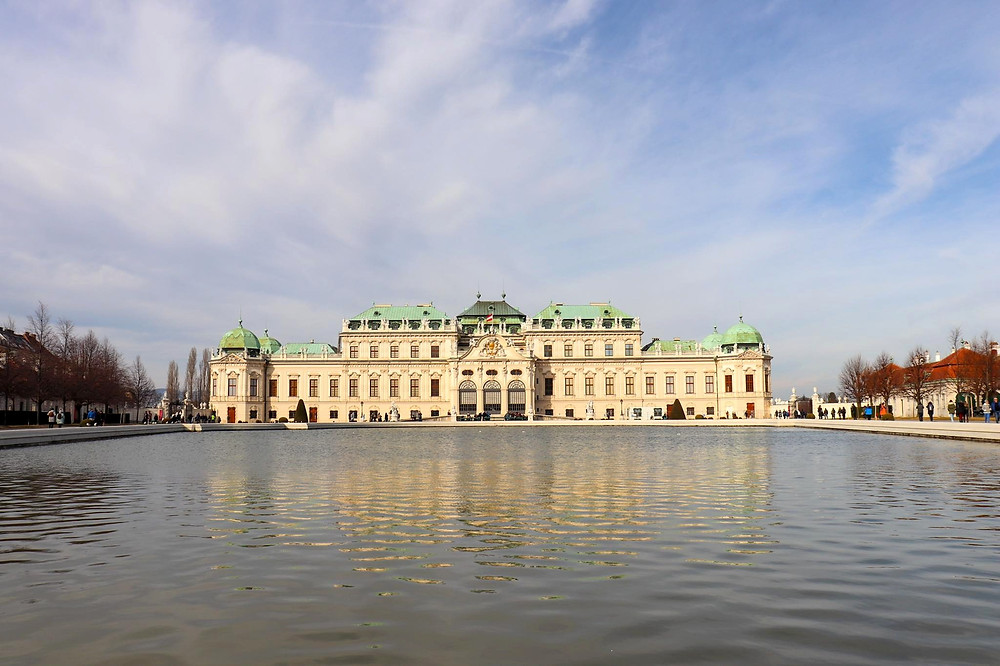 View of a palace in cream brick with green roofs and in front of it is a large pond reflecting the palace on the water.