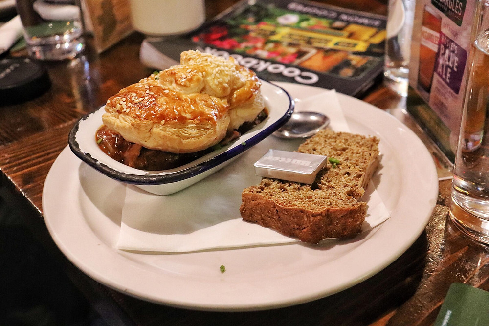 Beef and Guinness pie with a slice of bread in a pub in Dublin Ireland