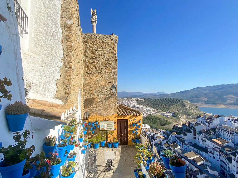 View of the city below of Iznajar from a viewpoint lined with blue plant pots on the wall, and a medieval tower at the end with a statue on the very top.