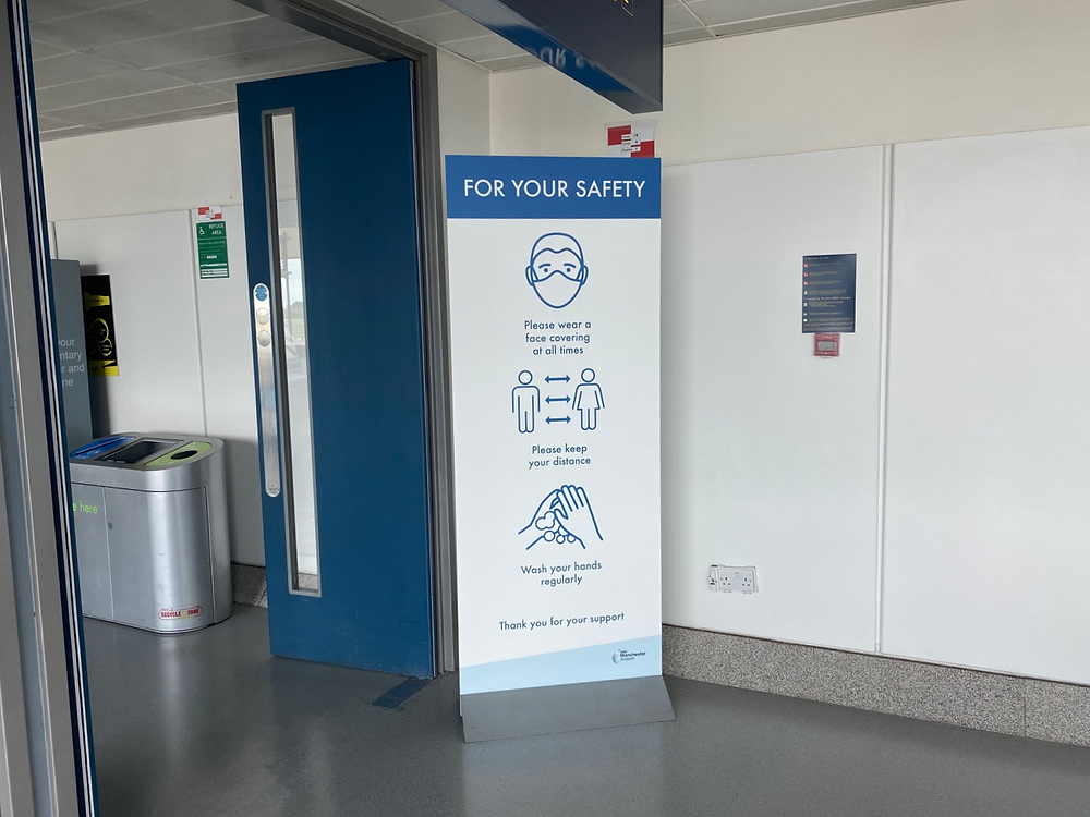 Safety banner about Coronavirus in terminal 3 at Manchester Airport