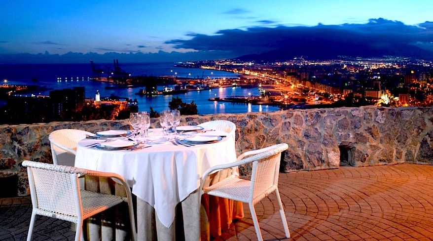 View of Malaga at night from a dining table sitting on a viewpoint with the city lights and port in the distance.