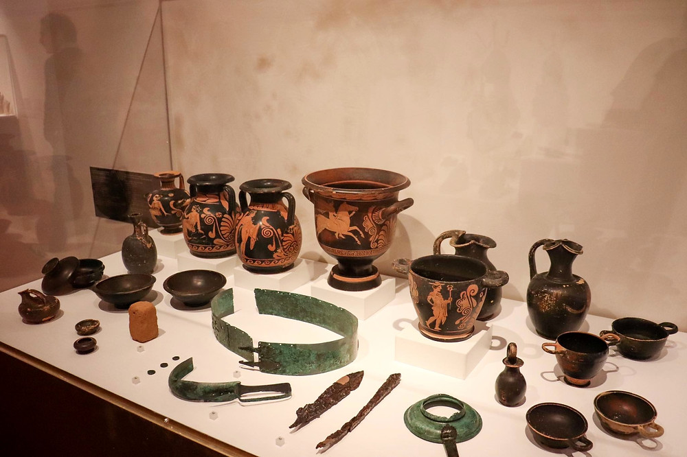 Various artifacts found in Pompeii such as vases, belts, and water jugs.