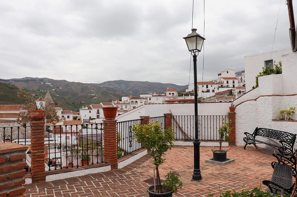 Benches placed around a small courtyard with a viewpoint of the white village, a lamp post sits in the middle of it.