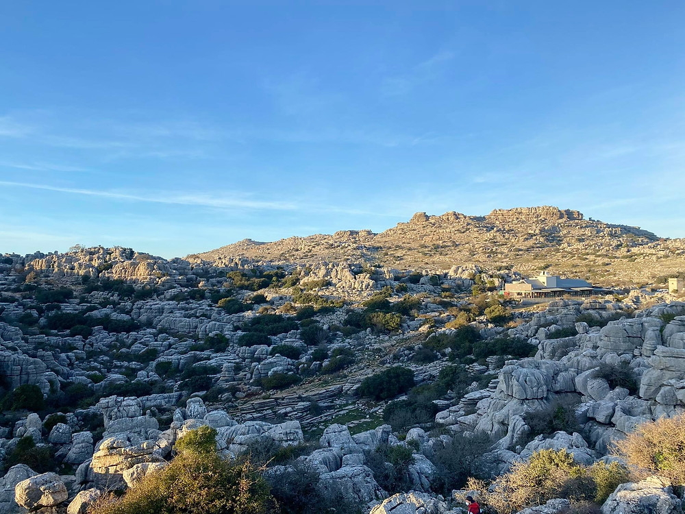 View of El Torcal from high up, showing the shadow caused by sunset and the visitor centre in the background.