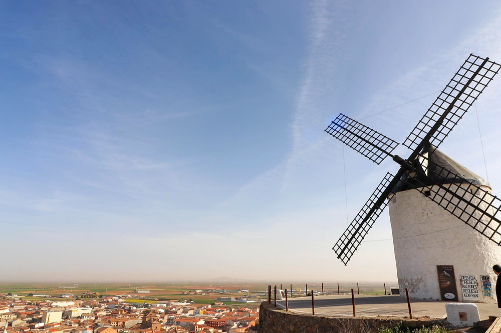 White windmill with a small circular parking lot in front of it on a sharp ledge overlooking a village.
