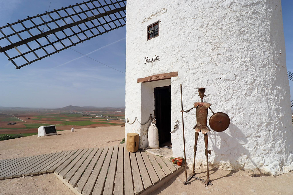 Bottom half of the white painted windmill with a open doorway and a iron statue of Don Quixote on the right.