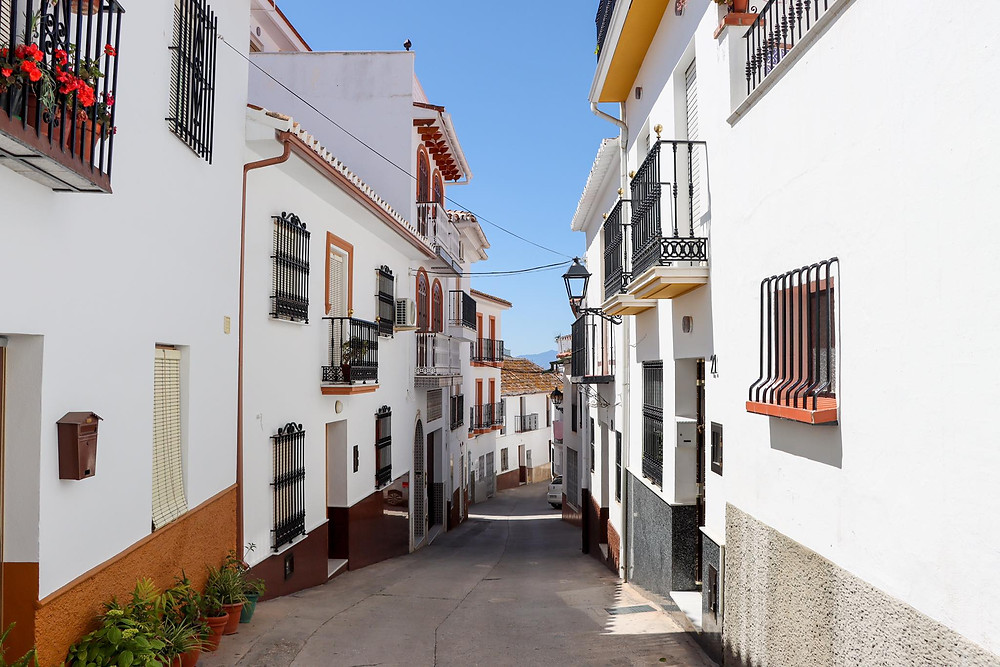 Narrow whitewashed street in Almogíá, partly in the shade.