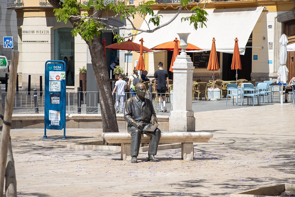 Statue of Picasso sitting on a bench in front of his place of birth.