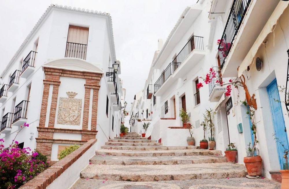 A whitewashed streets going uphill with steps in the middle.