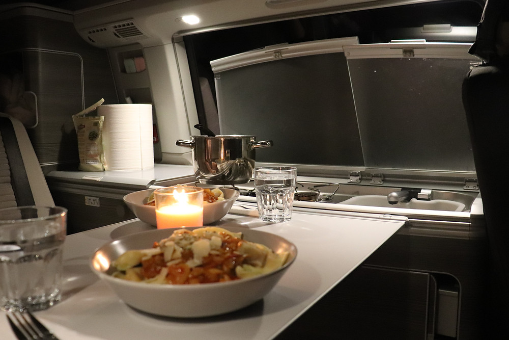 Pasta dinner inside the van with a candle in southern spain