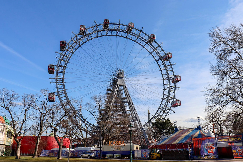 Vintage ferris wheel with large red boxes to sit in, standing at the beginning of an amusement part.