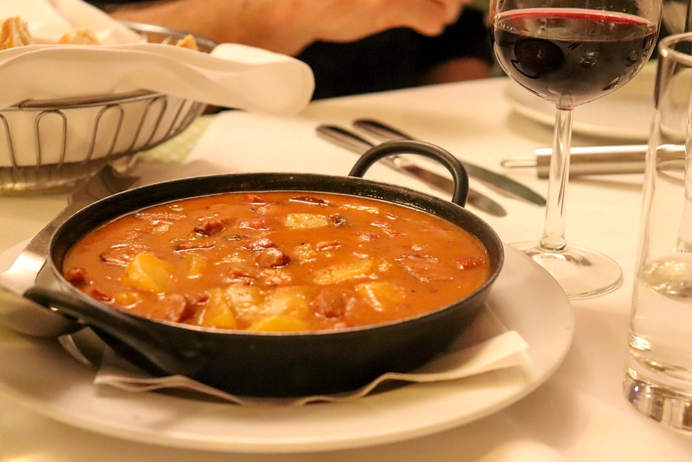 Traditional Austrian beef stew in an orange sauce with potatoes inside it.