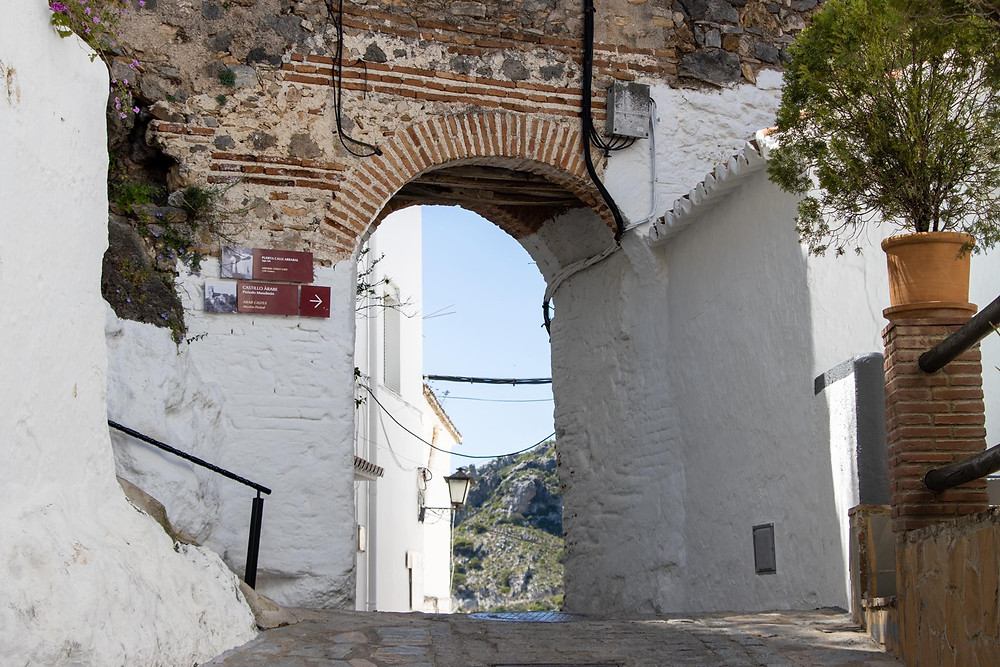 Medieval Arab arch mostly painted white with exposed brickwork at the top, placed in a narrow street.