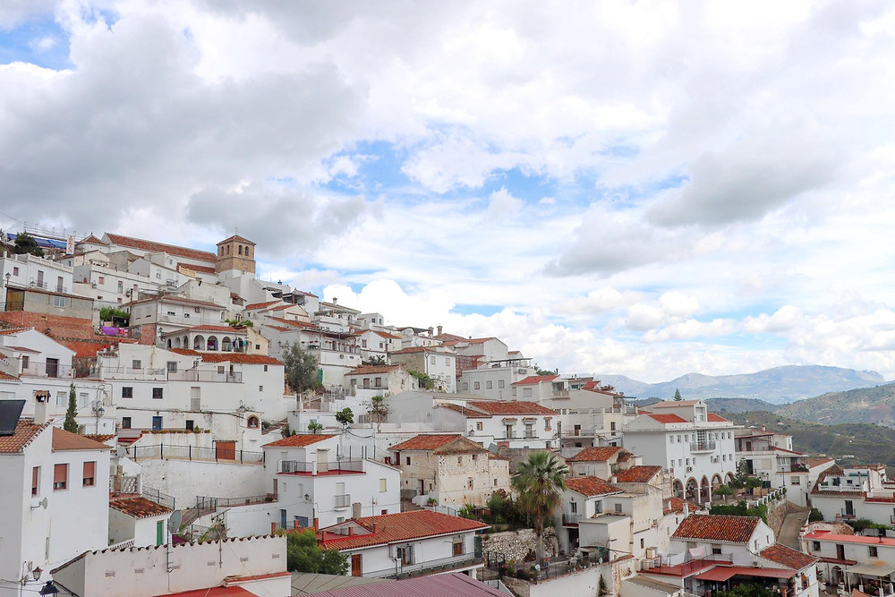 View of a white village going up the hillside on a cloudy day.