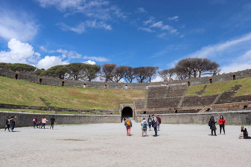 Inside the amphitheatre in Pompeii, grass is covering part of the stone stands.