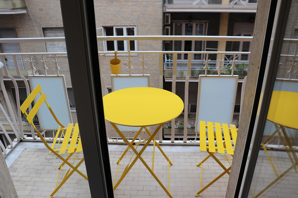Balcony with yellow table and chairs in B&B Via Toledo 156 Naples Italy