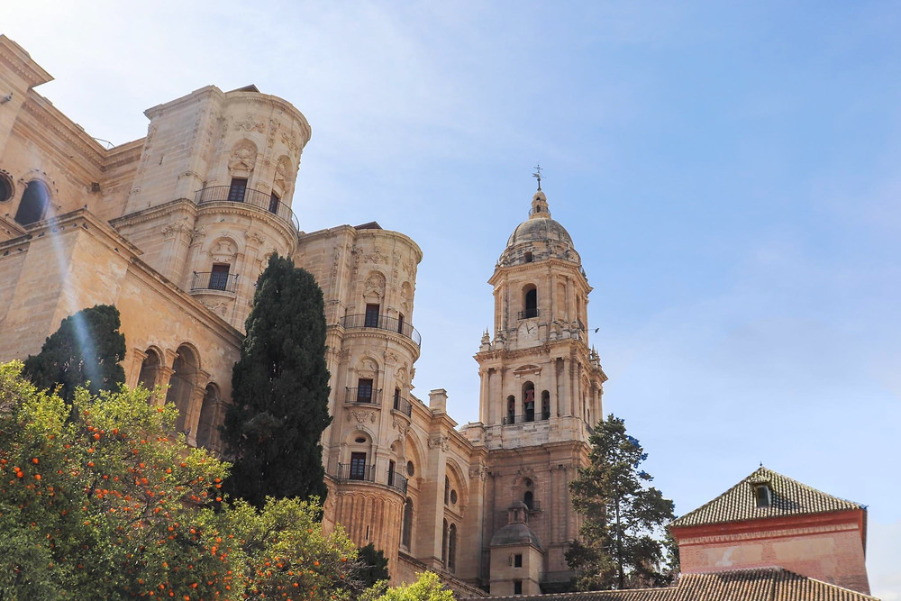View of Málaga's cathedral from below, showing the single tower against a blue sky.