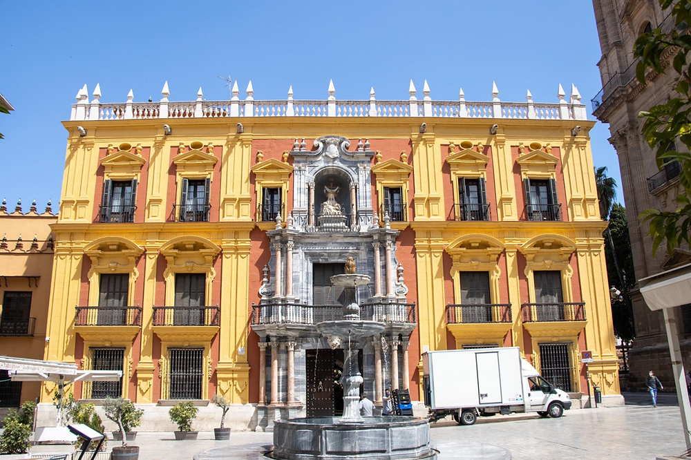 Yellow and red building with a water fountain in the middle of the plaza.